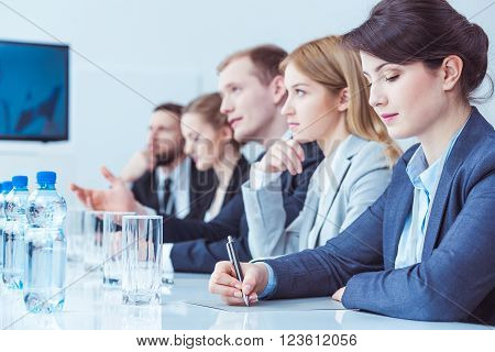 Firm management during business meeting sitting beside long desk in light office