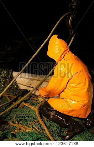 Trawl master repairs fishing trawl. Night time.