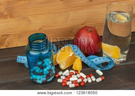 Glasses of water and fruit. Supplements and vitamins for the diet program. Food for weight reduction. Controlled diet.