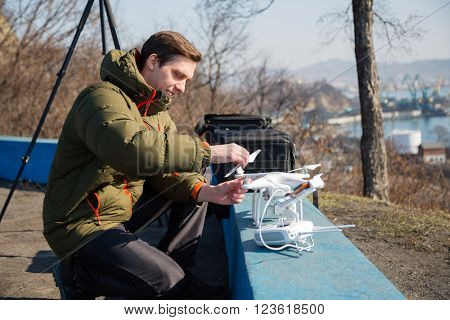 Young man prepares a drone to a controlled flight