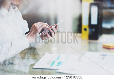 New business startup. Photo young businesswoman working new startup project modern office.Contemporary smartphone holding female hands and touching screen.Analyze statistics, plans table