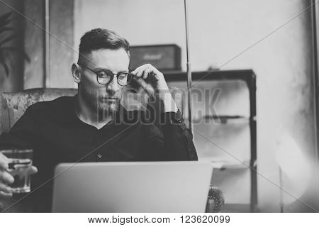 Bearded young businessman working on modern loft office. Man sitting in vintage chair, holding glass water. Using contemporary notebook. Black and white.