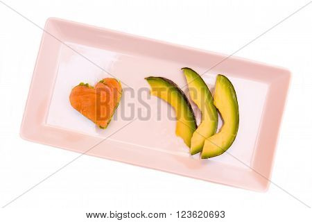 Tray with slices of avocado and salmon and avocado in a heart shape on white background seen from above