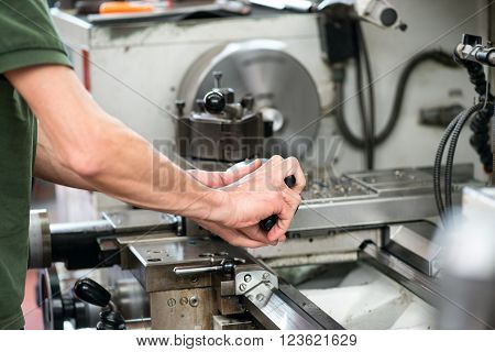 Blue collar or skilled workman working on a large industrial lathe guiding a component with his hands during manufacture