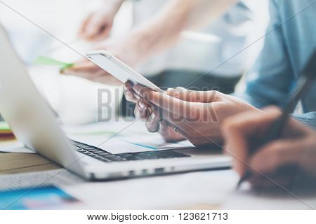 Closeup photo team job. Photo young business crew working with new startup project. Notebook on wood table, smartphone hands.Analyze plans, keyboard. Blurred background, film effect.