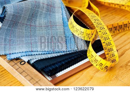 Sample fabric swatches on a tailors workbench with a yellow tape measure showing the tools of the trade in a close up view