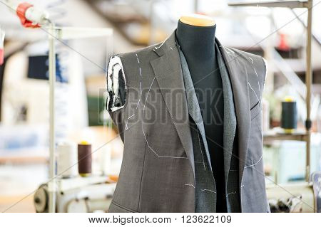 Half finished jacket in grey fabric displayed on a mannequin in a tailors shop close up view