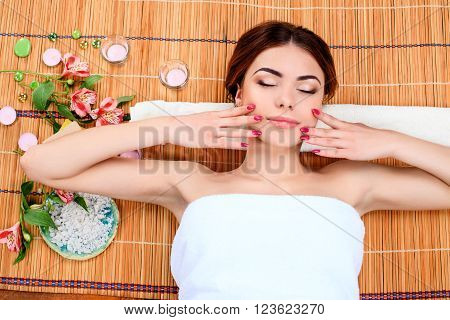 Beautiful young woman at a spa salon resting on a straw mat.