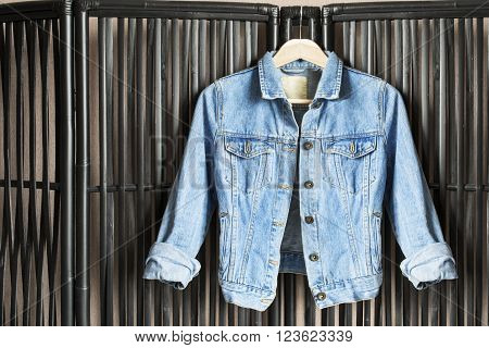Blue denim jacket on clothes rack hanging on bamboo screen