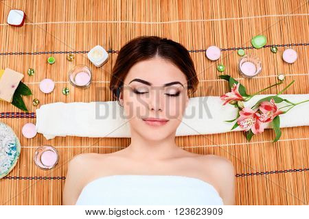 Beautiful young woman at a spa salon resting on a straw mat  with flowers