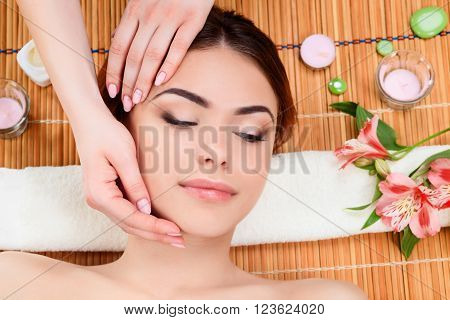 Beautiful young woman at a spa salon resting on a straw mat. Thegirl taking massages of face