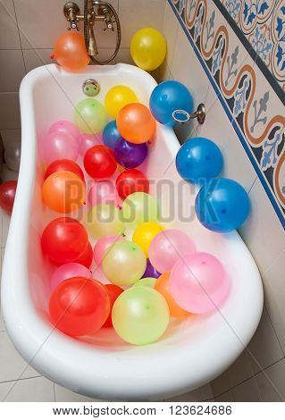 Bunch of colorful balloons in bath tube. Large pile of multicolored inflated balloons.