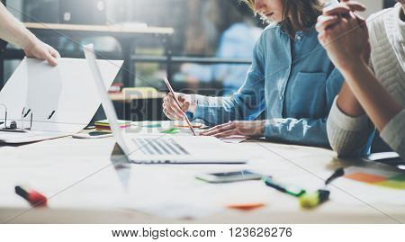 Coworking team. Photo young business crew working with new startup project. Notebook on wood table.  Woman using pencil. Blurred background, film effect
