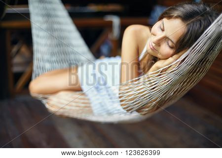Young beautiful woman sleeping in a hammock