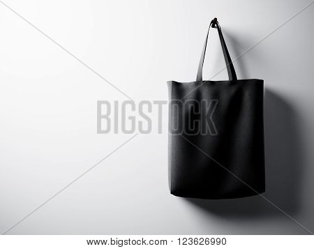 Photo black cotton textile bag hanging right side. Empty white wall background. Highly detailed texture.