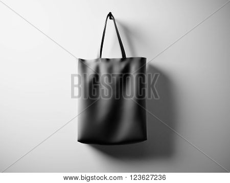 Photo black rubberized material bag hanging in center. Empty white wall background. Highly detailed texture, space for business message.