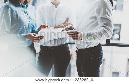 Business team meeting, work process. Photo professional crew working with new startup project. Project managers near window. Analyze business plans. Blurred background, film effect, bokeh.