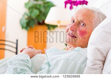Elderly patient laying in bed in a nursing home waiting for the doctor.