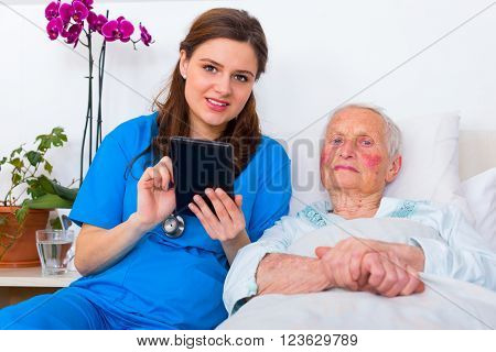 Caring doctor helping a senior patient to use a digital tablet.