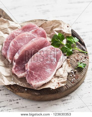 Raw pork chops on a rustic wooden cutting board