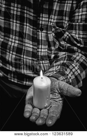 View of an old man hand holding a burning candle