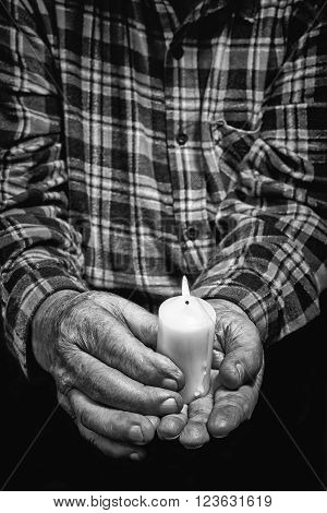 View of an old man hands holding a burning candle