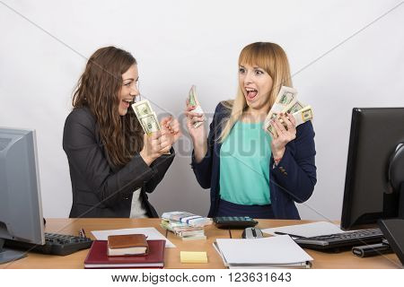 Two Happy Office Girl Happy Holding Wads Of Money In Their Hands