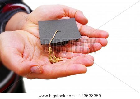 Student holding a miniature graduation cap in her hands isolated on white