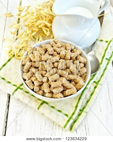 Oat bran large in bowl, a jug of milk, oat stalks on a kitchen towel on the background of wooden boards