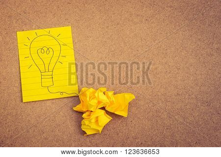 Hand writing light bulb on yellow paper on brown background with crumpled paper ball - business concept idea and strategy