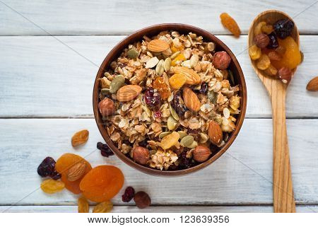Granola cereal flakes with dried fruit nuts and honey in a wooden bowl.