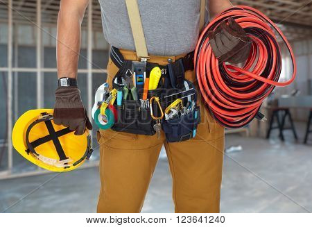 Electrician with construction tools and cable.