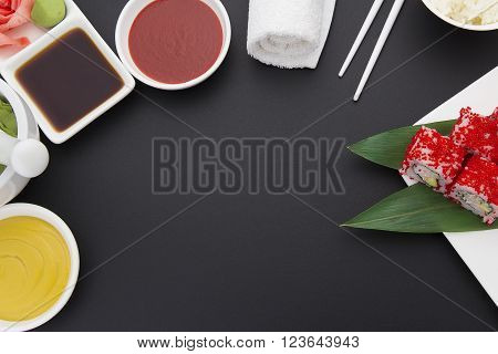 Japanese Cuisine. Sushi Roll With Red Tobiko On A White Plate With Ginger Wasabi And Sauces Over Bla