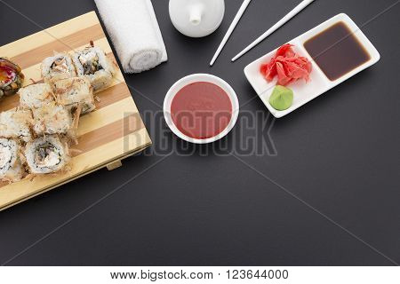 Shaving Tuna Sushi Roll On Wooden Plate ( Gete ) With Ginger Wasabi Chopsticks And Sauces Over Black