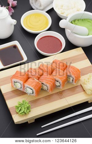 Japanese Cuisine. Sushi On A Wooden Plate With Ginger And Wasabi Over Black Background