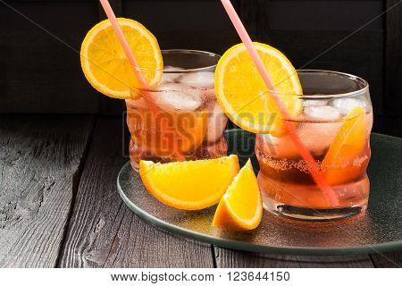 Aperitif aperol cocktail with orange slices and ice on a dark background