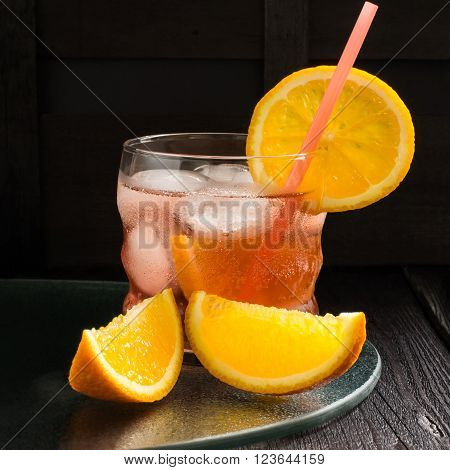 Aperitif aperol cocktail with orange slices and ice on a dark background. Selective focus, square image