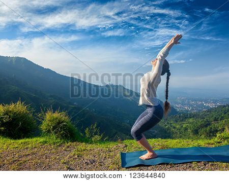 Young sporty fit woman doing yoga asana Utkatasana (chair pose) outdoors in mountains Himalayas in the morning. Himachal Pradesh, India