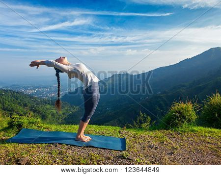 Young sporty fit man doing yoga Sun salutation Surya Namaskar pose Hasta Uttanasana outdoors in mountains