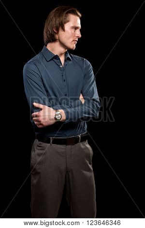 Man in blue shirt and grey slacks. Studio shot over black.