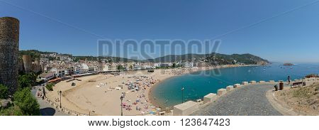 TOSSA DE MAR, CATLONIA, SPAIN - JUNE 19: Resort vacationers are visiting Platja Gran beach near ''Vila Vella enceinte'' on June 19, 2014 in Tossa de Mar, Costa Brava, Catalonia, Spain.