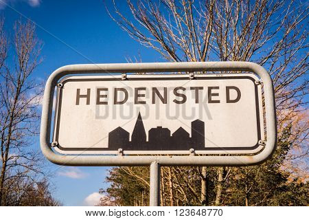 Hedensted city sign in Denmark with trees in the background