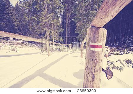 Vintage toned trail sign painted on perch, winter in Tatra mountains, Poland.