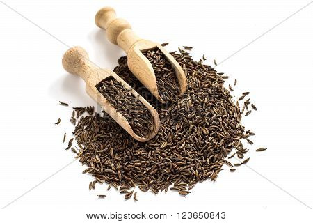 Dry cumin seeds in wooden scoops on a white background