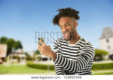 Portrait of young man making faces taking a selfie with urban  background