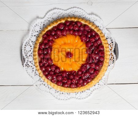 fruitcake with cherries and tangerines on white wood