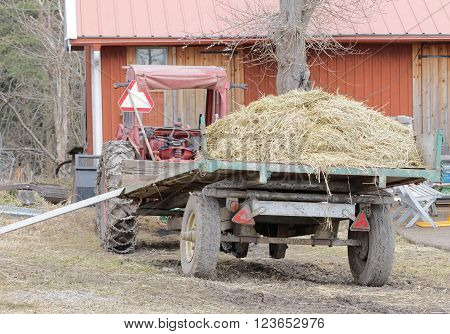 STOCKHOLM SWEDEN - MAR 20 2016: Old red tractor and a tractor trailer filled with hay at Oeverjarva Gard Mars 20 2016 Stockholm Sweden