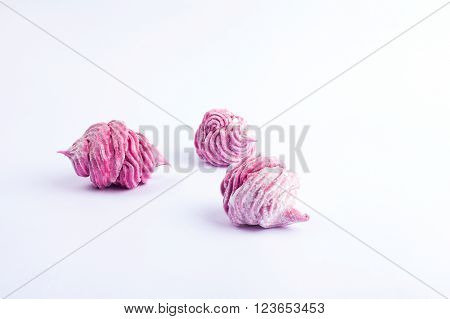 Delicious homemade sweet pink marshmallow with blackcurrant, dusted with icing sugar on a white background.