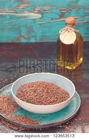 Linseed and linseed oil. Bowl of linseeds and bottle of linseed oil on rustic background, selective focus, blank space