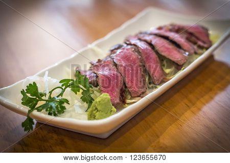 Japanese seared beef tataki served rare on bed of shredded lettuce